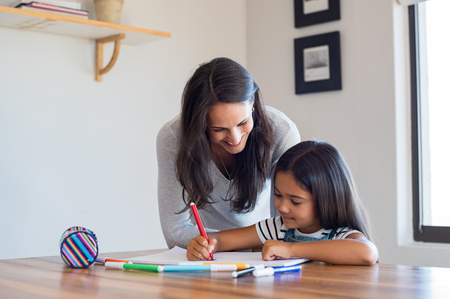 Foto de Happy mother and smiling daughter together painting using markers. Mother helping adopted child with art homework. Cheerful mother and asian little girl making painting at home. - Imagen libre de derechos