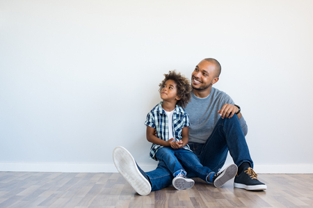 Photo pour African father and his son sitting on floor and looking up in a blank wall. Happy dad and little boy sitting in an empty room. Young black man with his child thinking and pensive with copy space. - image libre de droit