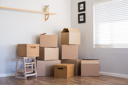 Foto de Stack of cardboard boxes in an empty room. Pile of carton boxes on the floor in an empty apartment. Stack of moving boxes in new house. - Imagen libre de derechos