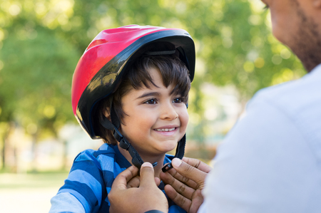 Foto de Father helping cheerful son wearing helmet for cycle. Excited little boy getting ready by wearing bike helmet to start cycling. Happy cute boy learn to ride a bike with his dad. - Imagen libre de derechos