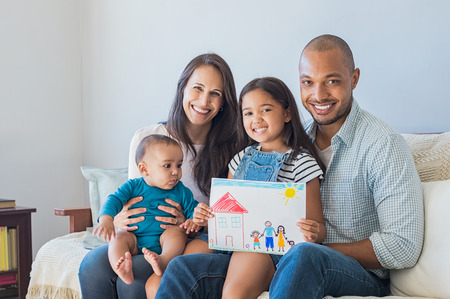 Photo pour Daughter showing drawing of a happy family outside a new house. Cute infant looking at colorful drawing of his sister. Happy proud multiethnic parents sitting with children on sofa  and looking at camera. - image libre de droit