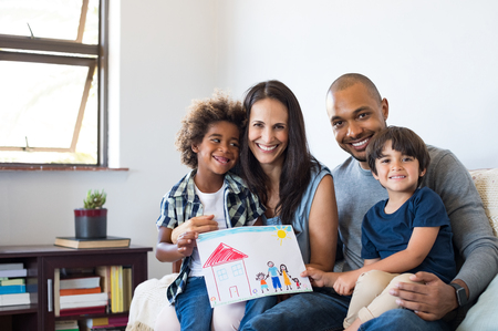 Foto de Proud parents showing family painting of son sitting on sofa at home. Smiling mother and father with children's drawing of a new home. Black little boy with his family at home showing a painting of a happy multiethnic family. - Imagen libre de derechos