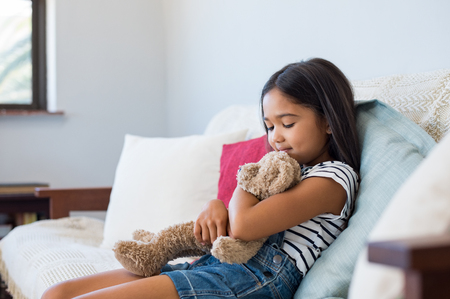 Photo pour Smiling young girl sitting on couch and embracing her teddy bear. Asian cute little girl hugging stuffed toy at home. Multiethnic female child playing with plush toy bear on the sofa. - image libre de droit