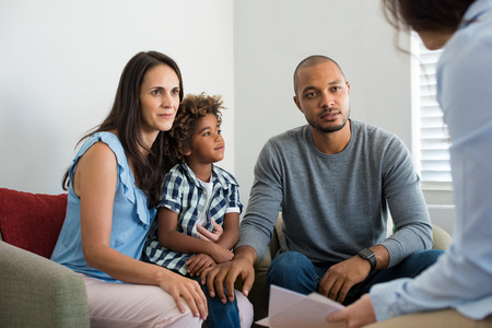 Photo pour Serious couple with son in a deep conversation with family counselor. Multiethnic parents talking about adoption with their counselor. Family at the financial planning consultation. - image libre de droit