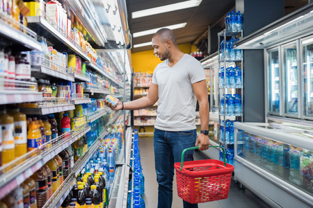 Foto de African man shopping in beverage section at supermarket. Black man doing shopping at market while buying cold drink. Handsome guy holding shopping basket reading nutritional values of product. - Imagen libre de derechos