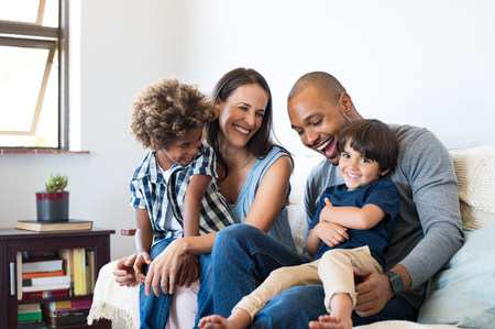 Photo pour Happy multiethnic family sitting on sofa laughing together. Cheerful parents playing with their sons at home. Black father tickles his little boy while the mother and the brother smile. - image libre de droit