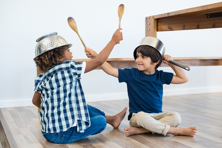 Photo for Little cute boys sitting on floor fighting with kitchen utensils. Happy multiethnic brothers wearing bowl and colander as helmet and wooden spoons as sword for play. Smiling children friends playing at home. - Royalty Free Image