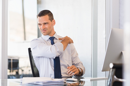 Photo pour Young businessman at work suffering from shoulder pain. Businessman holding shoulder and stretching after completion of work. Stressed businessman have back pain after long hours of work. - image libre de droit