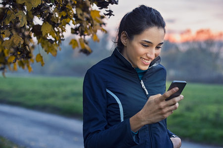 Foto de Young athlete looking at phone and smiling at park during sunset. - Imagen libre de derechos
