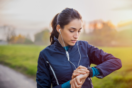 Foto per Young athlete listening to music during workout at park and adjusting smart watch. - Immagine Royalty Free