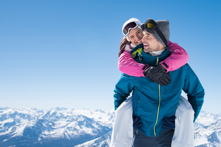 Foto de Happy man at the mountain giving piggyback ride to his smiling girlfriend. - Imagen libre de derechos