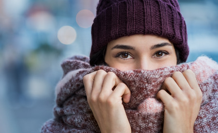 Foto de Winter portrait of young beautiful woman covering face with woolen scarf. Closeup of happy girl feeling cold outdoor in the city. Young woman holding scarf and looking at camera. - Imagen libre de derechos