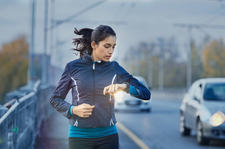 Foto de Young fitness woman runner checking time from smart watch. - Imagen libre de derechos
