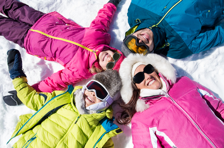 Photo for Happy young family lie on snow in winter holiday and looking at camera. - Royalty Free Image