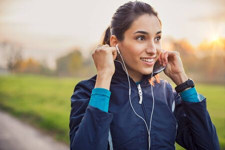 Photo for Young athlete adjusting jacket while listening to music at park. - Royalty Free Image