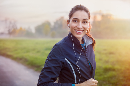 Photo pour Young beautiful woman listening music at park while running. - image libre de droit