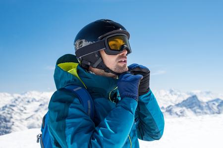 Photo pour Man skier wearing helmet and ski mask on snowy mountain. - image libre de droit