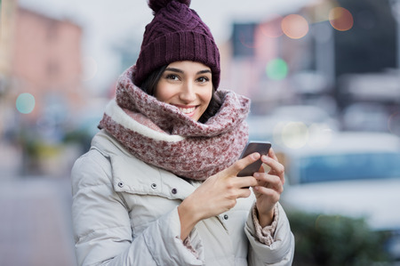 Photo for Happy young woman holding smartphone and looking at camera. - Royalty Free Image