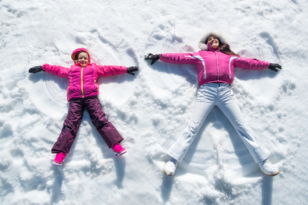Foto de High angle view of cute daughter and mother playing and lying in the snow. - Imagen libre de derechos