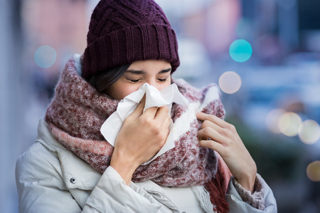 Photo pour Pretty young woman blowing her nose with a tissue outdoor in winter. - image libre de droit