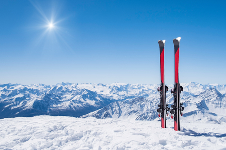 Foto de Red skis standing in snow with winter mountains in background. - Imagen libre de derechos