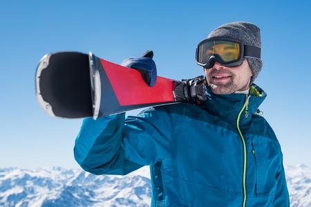 Foto de Happy skier holding a pair of skis and looking at the snowy mountains. - Imagen libre de derechos
