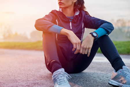 Photo for Young athlete sitting on ground to relax after jogging at sunset. - Royalty Free Image