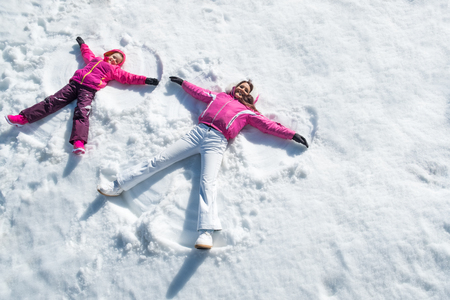Foto de Cheerful mother and daughter enjoying in snow while looking at camera. - Imagen libre de derechos