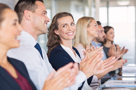 Photo for Businessmen and business women sitting in a row and applauding at meeting. Successful businesspeople clapping hands after presentation. Happy group of business people sitting in a row at conference. - Royalty Free Image