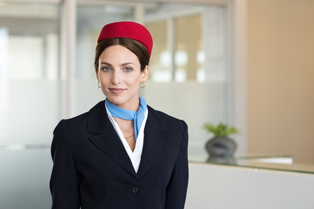 Foto de Portrait of young air hostess standing at airport and looking at camera. Portrait of flight assistant in uniform standing near check in counter. Happy agent wearing the hostess uniform at airport. - Imagen libre de derechos