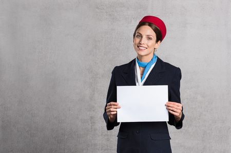 Foto de Young air hostess holding white placard isolated on grey background. Flight assistant holding blank sign and looking at camera. Woman stewardess with empty board and copy space. - Imagen libre de derechos