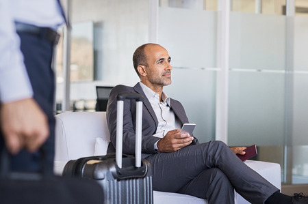 Photo pour Mature businessman expecting airplane at the airport. Thoughtful business man waiting for flight in airport. Formal business man sitting in airport waiting room with luggage and phone in hand. - image libre de droit