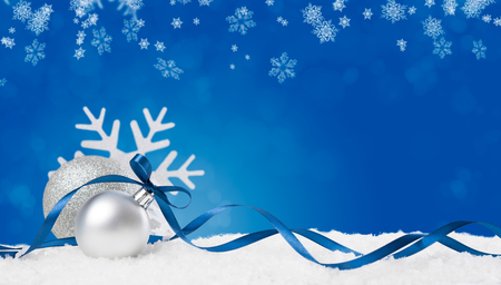 Foto de Christmas background in blue. Snow flakes and christmas balls with ribbon and copyspace. Xmas background with snowflakes, balls and ribbon. Write it on whatever you need. - Imagen libre de derechos