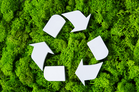 Foto de Top view of white recycle eco symbol on green moss with copy space. High angle view of recycled sign and eco concept on green background. Recycling and conservation of the environment sign. - Imagen libre de derechos