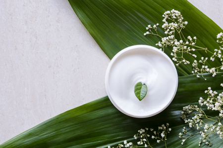 Foto de Top view of cosmetic lotion with white flowers and green leaf. Skin care beauty treatment with jar of body moisturizer. High angle view of white body lotion with little green leaf on marble background. - Imagen libre de derechos
