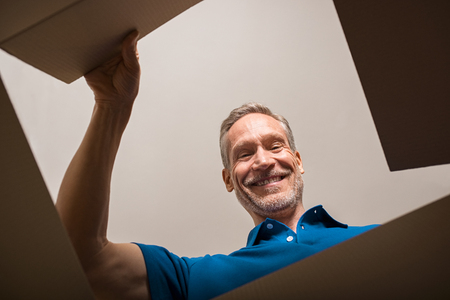 Photo pour Happy mature man looking into parcel cardboard box and smiling. Cheerful senior man happy on seeing package. Smiling man feeling overjoyed on seeing parcel and opening it. - image libre de droit