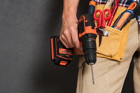 Photo pour Close up of handyman holding a drill machine with tool belt around waist. Detail of artisan hand holding electric drill with tools isolated over grey background. Closeup hand of bricklayer holding carpentry accessories. - image libre de droit