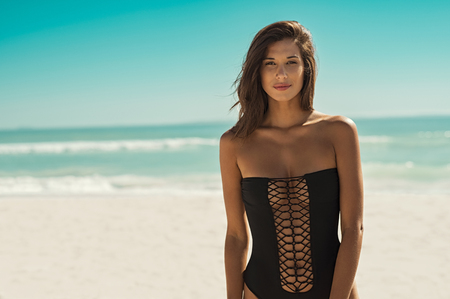 Foto de Beautiful fashion woman in black swimsuit looking at camera. Portrait of sensual girl in black swimwear standing on tropical beach. Portrait of sexy tanned woman walking at beach. - Imagen libre de derechos