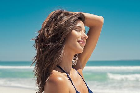 Foto de Closeup face of young woman with eyes closed enjoying breeze at beach. Portrait of carefree girl relaxing at sea. Beautiful smiling woman enjoying at beach the sun. - Imagen libre de derechos