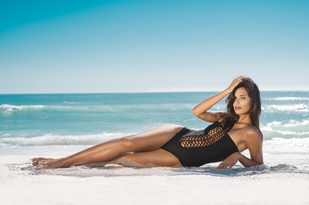 Foto de Fashion woman in black swimwear lying on tropical beach. Portrait of beautiful young woman lying on side enjoying sunbath near the sea shore. Sexy tanned girl in stylish swimsuit looking at camera. - Imagen libre de derechos
