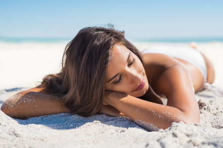 Photo for Relaxed woman lying down on sand during summer vacation. Beautiful girl lying down under the sun tanning in a tropical beach. Positive and serene young woman sunbathing at seaside with closed eyes.  - Royalty Free Image