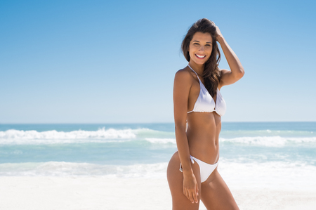 Photo pour Portrait of young woman in white bikini on tropical beach looking at camera. Beautiful latin girl in swimwear with copy space. Summer vacation and tanning concept. - image libre de droit
