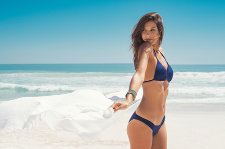 Photo pour Young woman waving white scarf in wind at beach. Latin happy girl in blue bikini holding tissue and looking away at sea. Sexy fashion woman playing with the scarf on seashore.  - image libre de droit