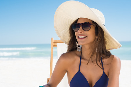 Photo pour Young woman in blue bikini sitting on deck chair wearing white straw hat. Happy girl enjoying summer vacation at beach. Portrait of beautiful latin woman relaxing at beach with sunglasses looking away. - image libre de droit