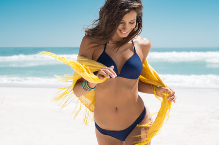 Foto de Beautiful young woman running on the beach with a yellow tissue. Happy smiling girl with scarf enjoying at beach. Freedom and carefree concept. - Imagen libre de derechos