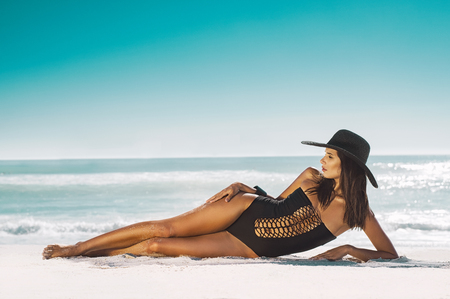 Foto de Fashion young woman in black swimsuit and straw hat lying on side at beach. Beautiful tanned girl lying on sand. Attractive girl wearing glamour swimwear on tropical beach while sunbathing. - Imagen libre de derechos