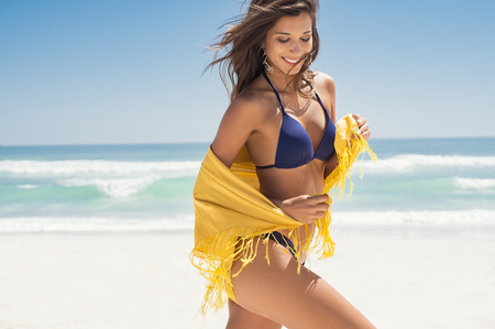 Photo for Young woman in bikini holding a yellow scarf on windy beach. Happy girl draped in yellow tissue and walking on beach with copy space. Cheerful woman enjoying summer while running at sea. - Royalty Free Image