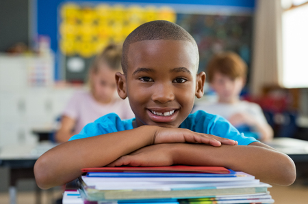 Foto de Portrait of african american schoolboy leaning on desk with classmates in background. Happy young kid sitting and leaning chin on stacked books in classroom. Portrait of elementary pupil looking at camera. - Imagen libre de derechos