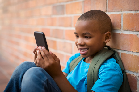 Photo pour Happy african student wearing green bagpack and using smartphone at school. Smiling cute boy playing with smart phone while sitting on floor. Cheerful child making video conversation on cell phone. - image libre de droit
