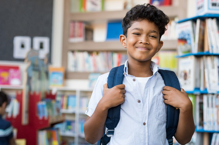 Foto de Portrait of smiling hispanic boy looking at camera. Young elementary schoolboy carrying backpack and standing in library at school. Cheerful middle eastern child standing with library background. - Imagen libre de derechos